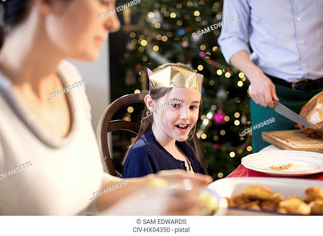 Smiling girl wearing paper crown at Christmas dinner