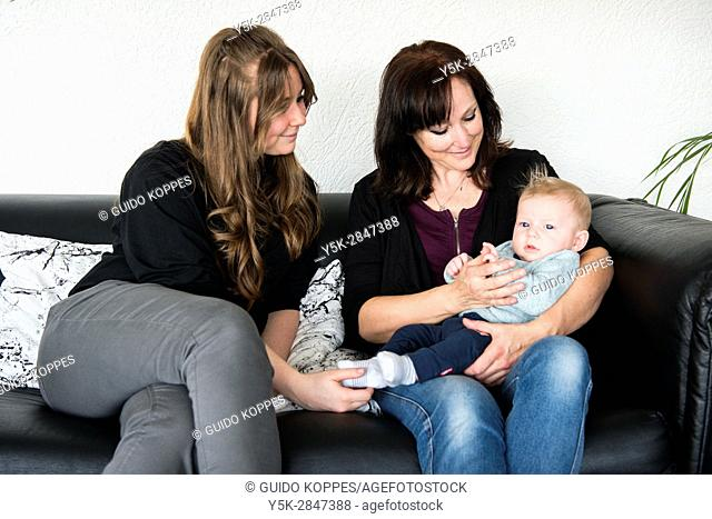 Zwijndrecht, Netherlands. Grandmother, young adult mother and a baby son being together while sitting at their living room couch