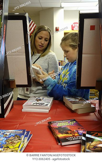 6th Grade Girl and Teacher Conferring in School Library, Wellsville, New York, USA