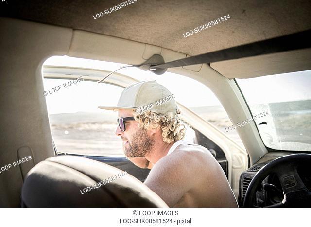 A male surfer sitting in his car at Corralejo in Fuerteventura