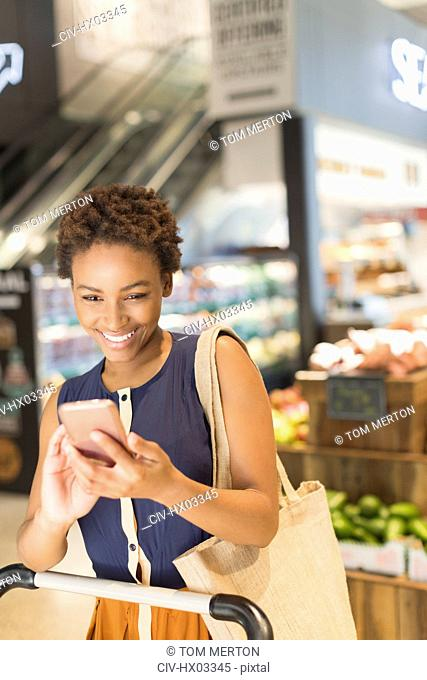 Smiling young woman using cell phone in grocery store market