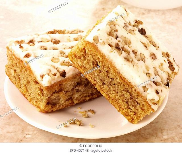 Two pieces of carrot cake with cream cheese icing & walnuts