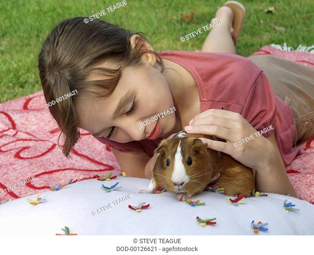 Girl lying on rug with brown and white guinea pig