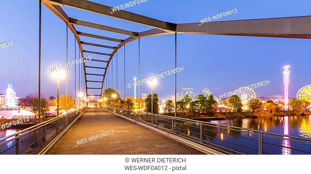Germany, Stuttgart, lighted Cannstatter Wasen fairground with footbridge in the foreground
