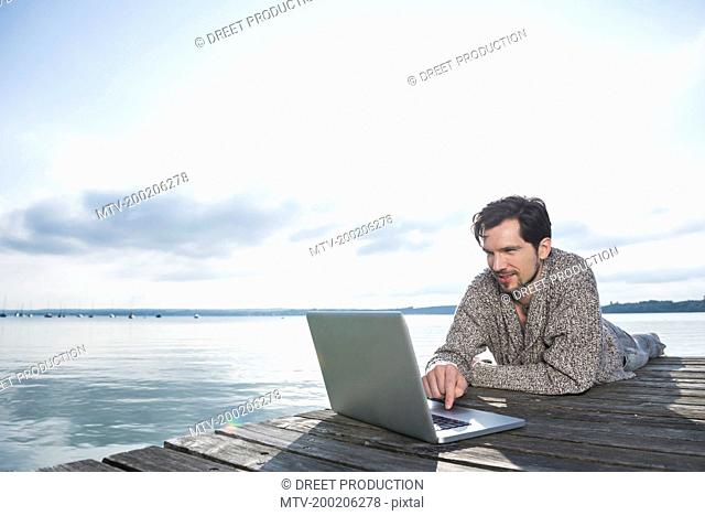 Man outdoors lake working laptop computer