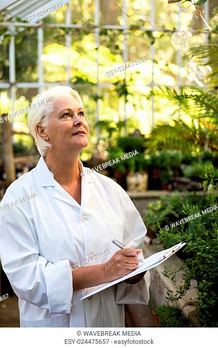Female scientist writing in clipboard while examining plants