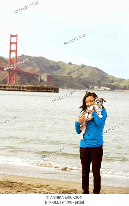 Chinese girl holding dog on beach