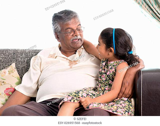 Portrait of Indian family at home. Grandparent and grandchild chatting. Asian people living lifestyle. Grandfather and granddaughter