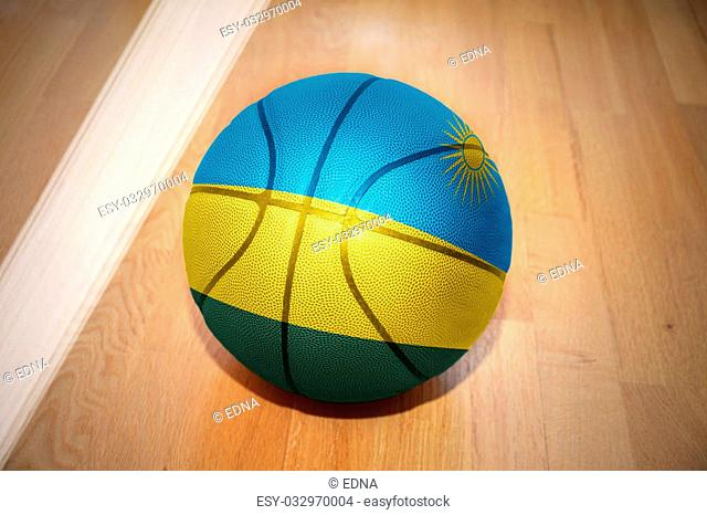 basketball ball with the national flag of rwanda lying on the floor near the white line