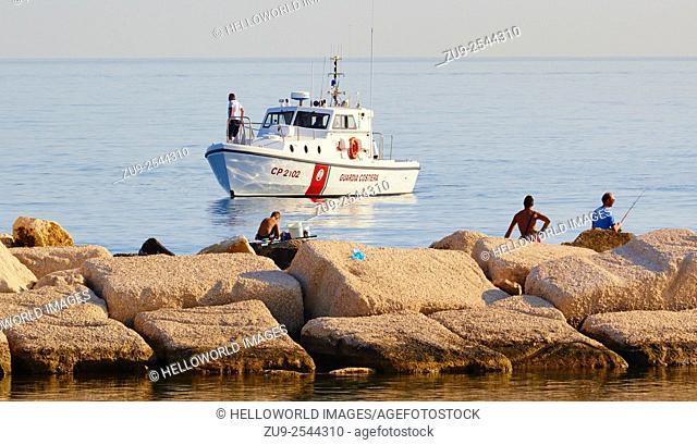 Boat of the Guardia Costiera, Italy's coastguard, moored off the coast near fishermen, Molfetta, Puglia, Italy, Europe