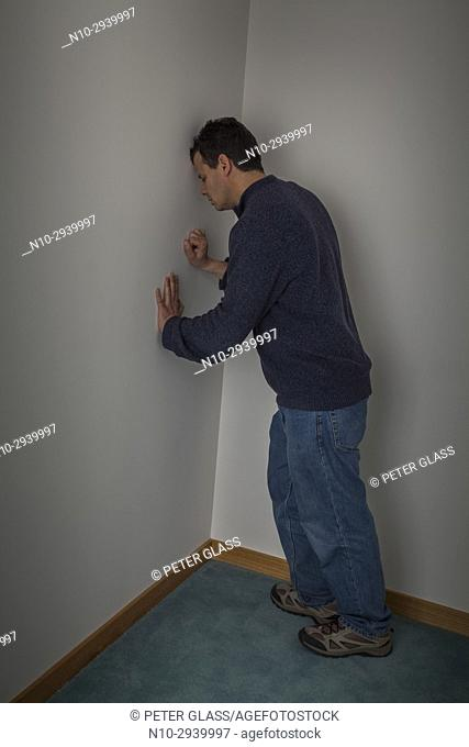 Middle age man leaning against wall in the corner of a room