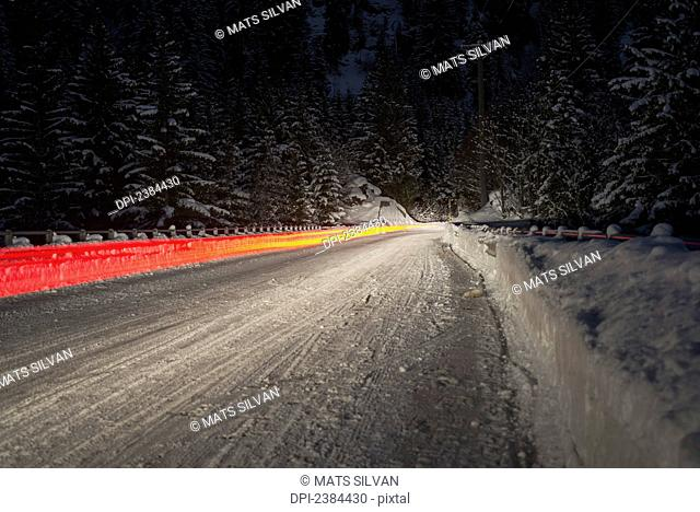 Light trail from a vehicle taillight on a snowy road at nighttime; Ticino, Switzerland