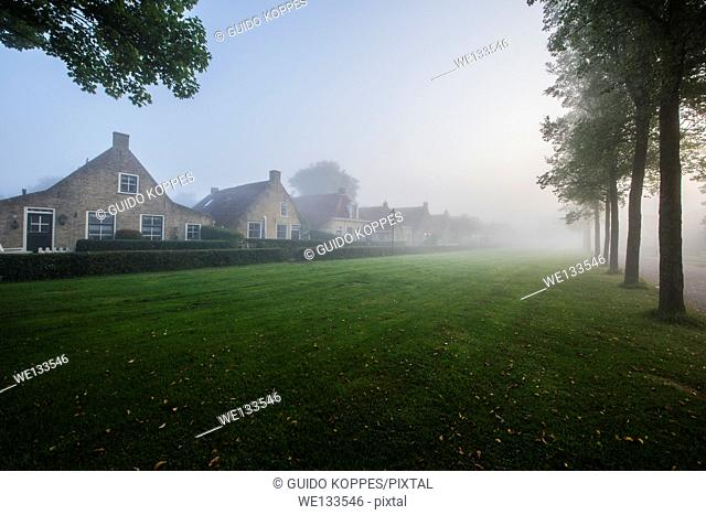 Schiermonnikoog, Netherlands. Meadow in a small island village covered in morning fog