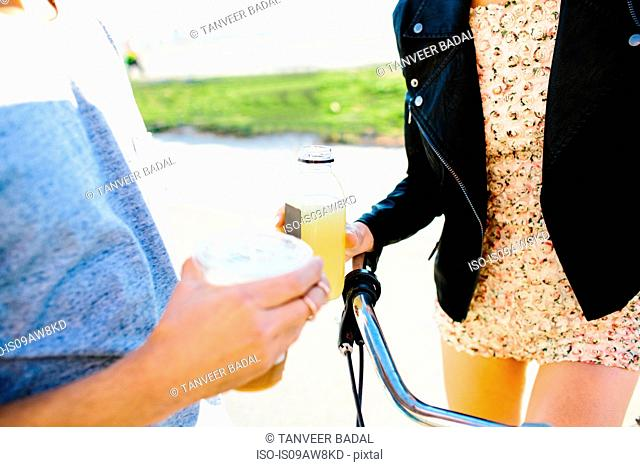 Cropped shot of young couple holding juice and coffee drinks at coast
