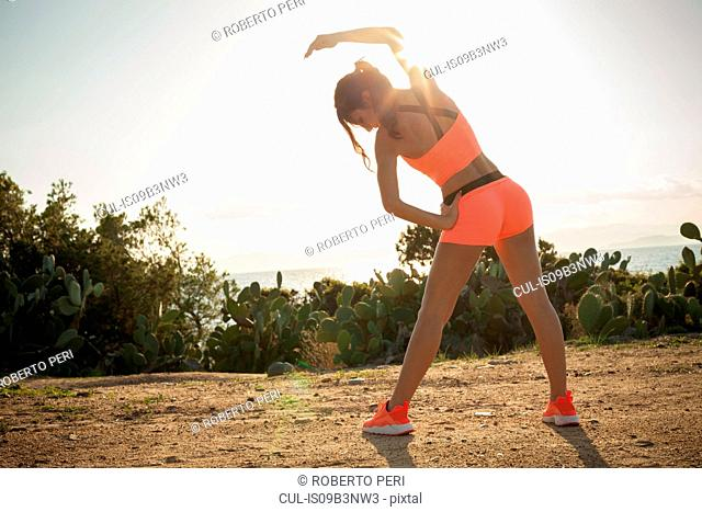 Young woman exercising outdoors, stretching, rear view