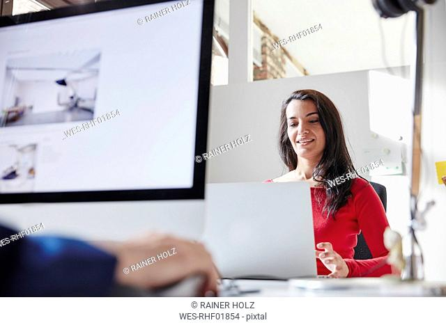Businesswoman and colleague working together in office