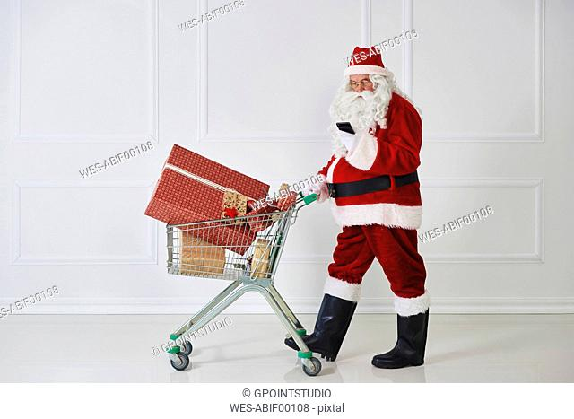 Santa Claus carrying Christmas presents in a shopping cart while looking at cell phone