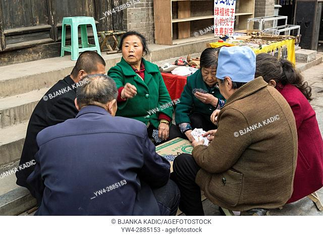 Group of people playing cards in the street, Pingyao, Shanxi province, China