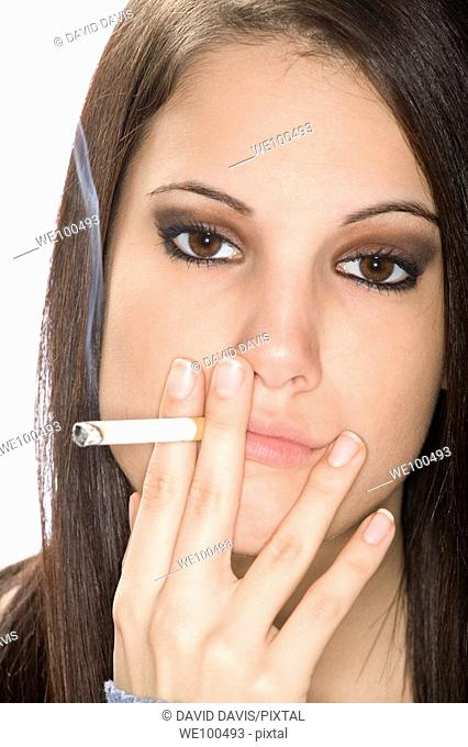Caucasian woman smoking a cagarette on a white background