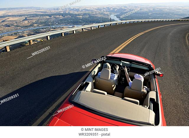 Young Caucasian couple on a road trip in their convertible sports car near Lewiston, Idaho USA