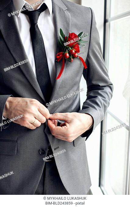 Caucasian man wearing corsage fasting suit jacket button
