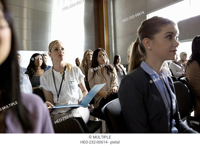Attentive students listening in lecture audience in auditorium