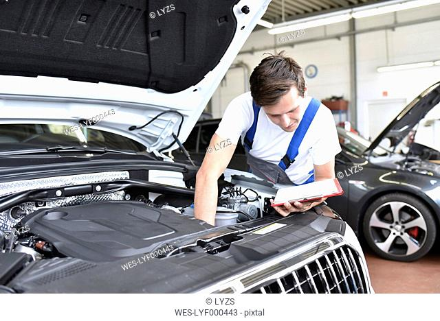 Mechanic examining engine of a car in a garage
