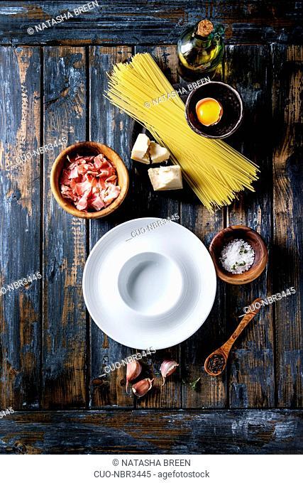 Ingredients for traditional italian pasta alla carbonara. Uncooked spaghetti, pancetta bacon, parmesan cheese, egg yolk, salt, pepper