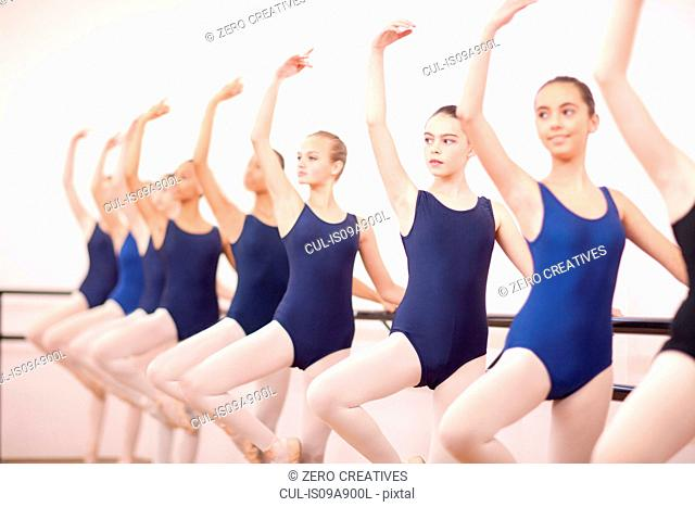 Row of teenage ballerinas with arms outstretched