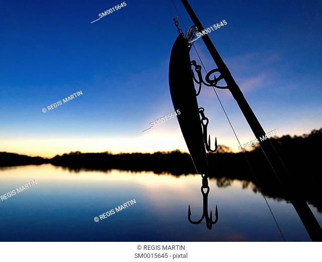 Silhouette of a fishing lure and fishing rod against a sunrise over Tommy Cut Creek, in the Northern Territory of Australia