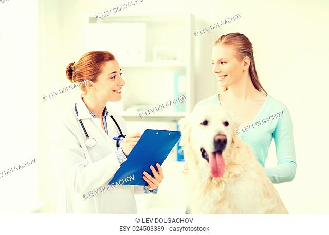 medicine, pet, animals, health care and people concept - happy woman with golden retriever dog and veterinarian doctor writing to clipboard at vet clinic