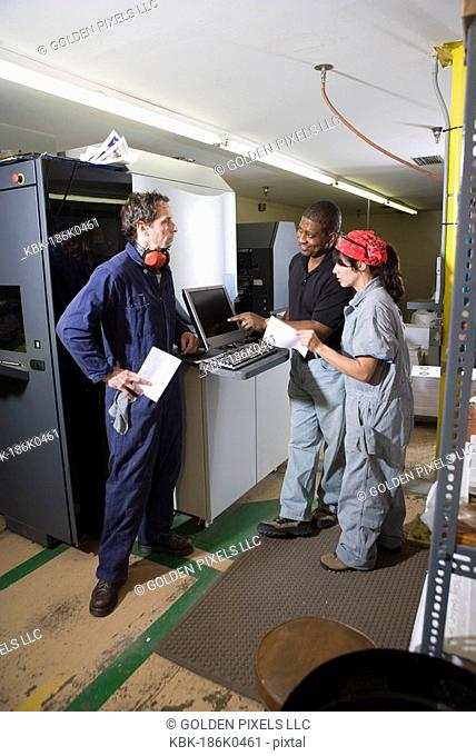 Workers being trained to use a piece of machinery with computer controls