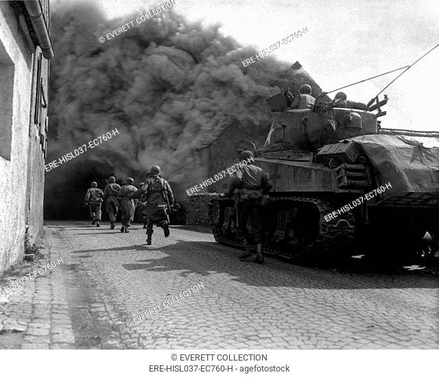 U.S. infantrymen running through the smoke-filled streets of Wernberg, Germany. 55th Armored Infantry Battalion and tank of the 22nd Tank Battalion