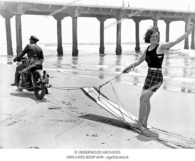 Manhattan Beach, California: c. 1930.Here's what they do when there isn't a boat available for aquaplaning. The Manhattan Beach Chief of Police gives a ride at...