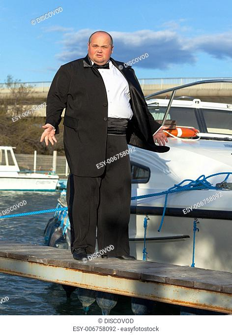 Overweight man in tuxedo standing on the deck of a luxury pleasure boat