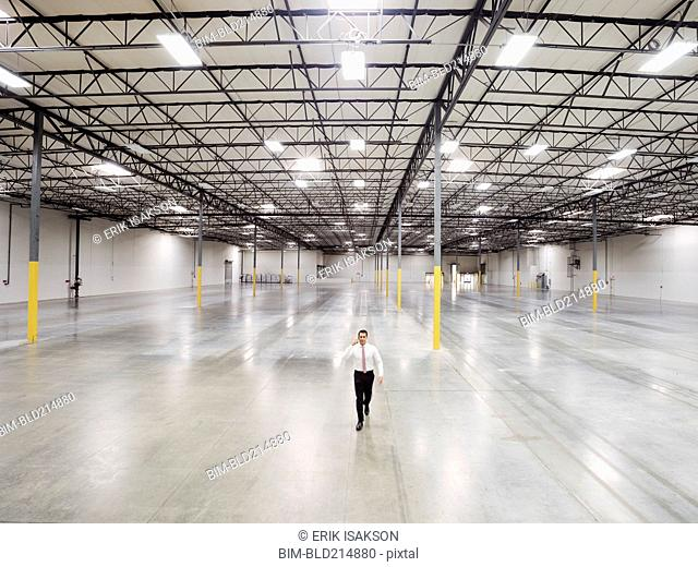 Caucasian businessman walking in empty warehouse