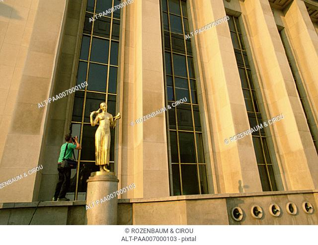 France, Paris, person photographing statue in front of Chaillot Palace