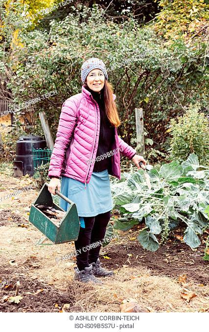Woman working in garden holding box of garden tools