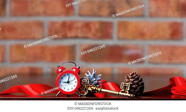 Red alarm clock and gold christmas key with other on brick wall background
