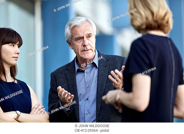 Senior businessman gesturing and talking to colleagues