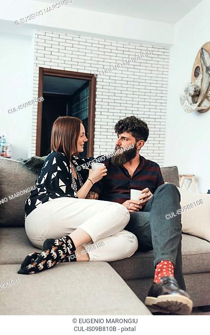 Couple relaxing with coffee on sofa