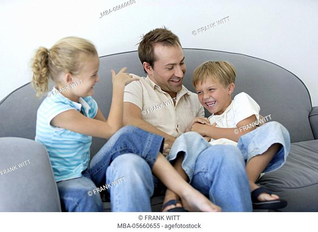 Father and 2 children are romping around on sofa