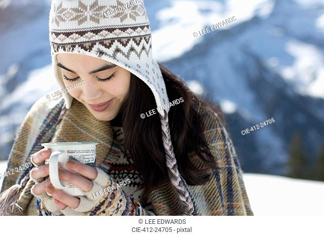 Smiling woman in knit hat drinking hot cocoa outdoors