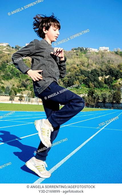 Child execising on track and field