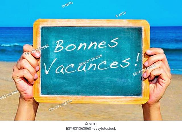 someone holding a blackboard on the beach with the sentenece bonnes vacances, happy vacations in french, written on it