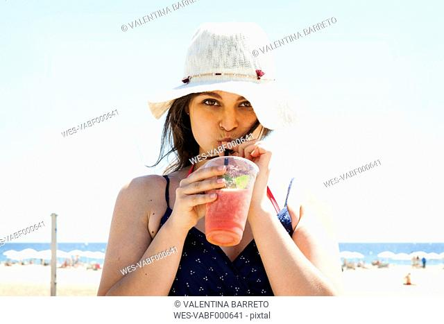 Young woman drinking cocktail on the beach