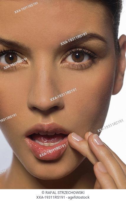 Woman applying vaseline on lips