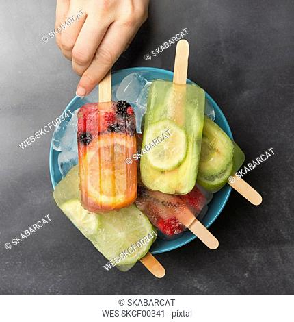 Woman's hand taking orange berry popsicle
