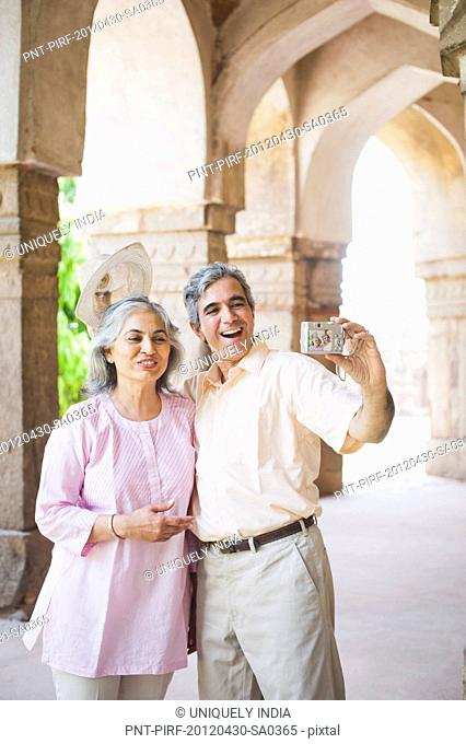 Mature couple taking picture of themselves with a digital camera, Lodi Gardens, New Delhi, India