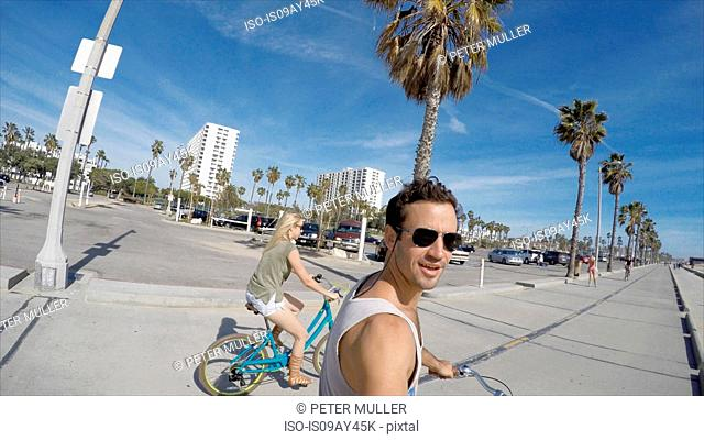 Man taking selfie cycling at Venice Beach, California, USA